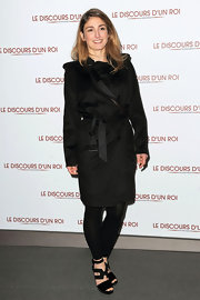 Julie stays bundled in a black trench coat while on the red carpet.