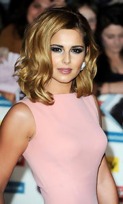 Cheryl Cole attended the Pride of Britain awards wearing sultry, smoky eye makeup. To try out her sexy look, begin by sweeping black eye pencil along the top and bottom lash lines and on the inner rims of eyes. Next, apply a deep metallic gunmetal gray to upper lids and blend up into the creases. Then add a softer metallic sliver shadow to the inner corners of they eyes and under the brow bone. To finish, apply several coats of a volumizing mascara.