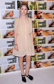Saoirse paired a nude colored dress with clunky black ankle boots.