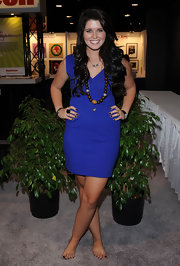 Katherine balanced her bright blue mini dress with earthy wooden beads.