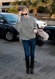 Charlize Theron balanced the loose silhouette of her sweater with boots and fitted jeans.