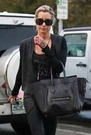Ashley Tisdale jazzed up her streetwear with luxe accessories including a black Celine black and studded fingerless Chanel gloves.