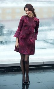 Olga went for a flirty mod look in this plum brocade cocktail dress with belled sleeves at the 'Oblivion' photocall.