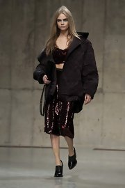 Cara Delevingne carried a chain strapped velvet purse as she walked the runway at the Unique show at LFW.