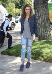 Zendaya Coleman arrived for an event dressed down in a blue zip-up jacket and a gray tee.