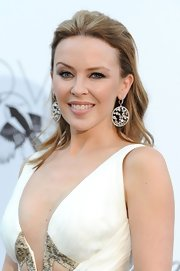 Kylie Minogue partially swept back her half up, half down do.