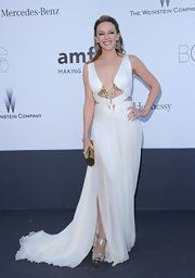 Kylie Minogue stunned in a flowing white gown with cutout detailing, a plunging neck, and golden embellishments.