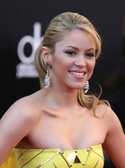 Shakira showed off a twisted pair of diamond drop earrings with her hair pulled up into a curly ponytail. Small bangs were pushed to one side and framed her face.