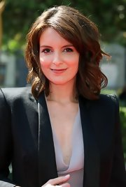 Tina's hair is styled down with large sexy waves that look great with her top and bold shouldered blazer.