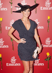 Natalie looks stunning in this polka-dot dress and wide-brimmed feather hat. Perfect attire for the Emirates Cup Day.