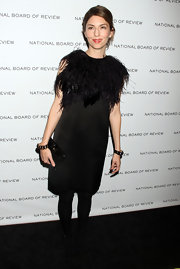 Sofia kept the focus on her feathered frock by complementing it with a polished black snakeskin clutch.
