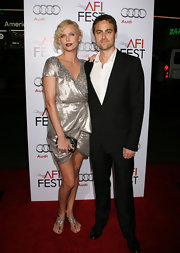 Charlize dressed down her metallic retro dress with a pair of sparkly silver thong sandals.