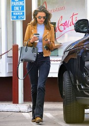 Alessandra Ambrosio went on a coffee run wearing a camel-colored suede jacket over a gray knit top.