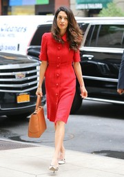 Amal Clooney headed out in New York City looking stylish in a red tweed shirtdress by Dolce & Gabbana.