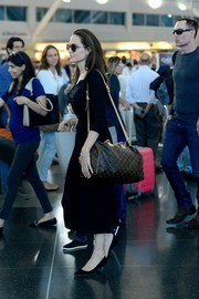 Angelina Jolie touched down at JFK carrying a Louis Vuitton duffle.