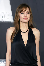 Angelina topped off her draped navy dress with a green gemstone collar necklace.