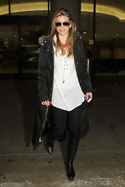 AnnaLynne buncles up at the airport in an ankle-length down jacket with a fur trimmed hood.
