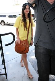 Ashlee Simpson paired her yellow tee with a tan cross body bag.