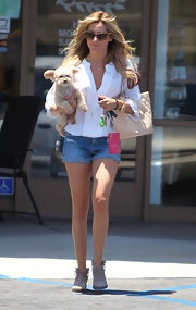 Ashley carried her pup in one hand and a hot pink patent wallet in the other.