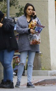 Mila Kunis paired her cardigan with ripped jeans.