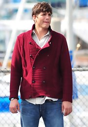 Ashton was spotted wearing a burgundy chunk cable knit cardigan over a button up shirt and jeans.
