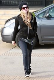 Avril is wearing a black cable beanie with shield-shaped sunglasses.