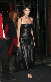 Bella Hadid went vampy in a black spaghetti-strap leather dress by Dior for a night out in New York City.