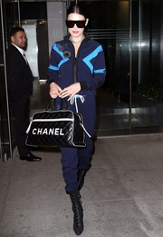 Bella Hadid matched her jacket with a pair of blue Mr&Mrs Italy track pants.
