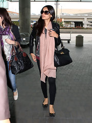 Freida Pinto traveled in style with a black leather flap tote slung over her arm.