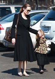 Angelina Jolie looked classic and sophisticated in a wool riding coat with a full circle skirt and padded shoulders while taking her children to a museum.