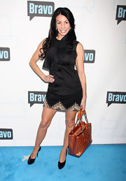 """Real House Wives"" star Danielle Staub came out strutting her stuff at a Bravo party where she rocked a black dress studded at the hemline. She paired her flirty frock with a tan patent leather tote."