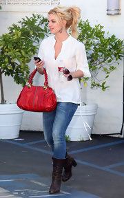 Britney Spears added a dash of color to her look with a bright red shoulder bag.