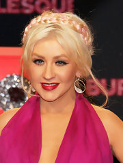 Christina highlighted her traditional hairstyle with silver hoop earrings complete with decorative wings.