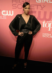 Tyra is supermodel glamorous on the red carpet in a black silk jumpsuit with sequin shoulder embellishments.