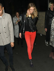 Rosie Huntington-Whiteley went to a Coldplay concert decked out in cherry red jeans and black suede ankle boots featuring subtle silver detailing.