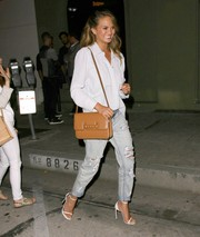 Chrissy Teigen added a dose of sexiness to her boyish look with a pair of white slim-strap sandals.