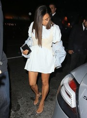 Kim Kardashian sported a cream-colored corset for added shape to her baggy tee.
