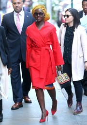 Lupita Nyong'o looked striking in a fringed and belted red coat as she arrived for her 'Good Morning America' appearance.