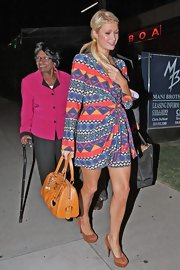 Paris Hilton paired her vibrant wrap dress with tan suede platform pumps.