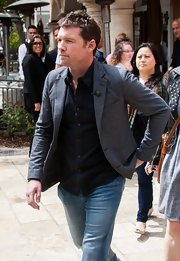 Sam Worthington chose a standard gray blazer and button down for his casual but slightly dressy look on the set of 'Extra.'