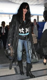 Cher looked like she just stepped out of a Western film in her black moto boots, leather coat, and hat combo.