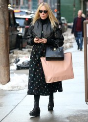 Chloe Sevigny went shopping in New York City wearing a black leather jacket over a printed midi dress.
