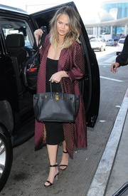Chrissy Teigen traveled in elegant style wearing a dotted purple silk coat.