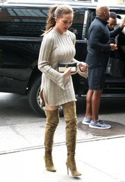 Chrissy Teigen polished off her chic cold-weather look with olive-green thigh-high boots by Jimmy Choo.
