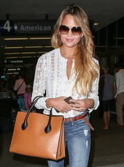 Chrissy Teigen looked a little shy in her oversized square shades while making her way through LAX.