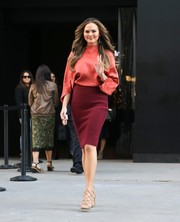Chrissy Teigen mixed colors so stylishly with this burdundy pencil skirt and coral blouse combo.