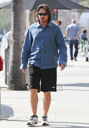 Christian Bale paired a classic button-down shirt with athletic shorts for a day with his family in California.