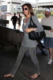 Cindy Crawford paired her grey jeans and cardigan with a black leather shoulder bag.