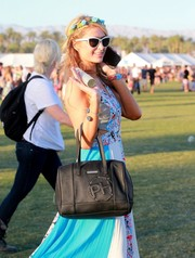 Paris Hilton strutted around on day 3 of Coachella carrying a black leather bowler bag from her own line.
