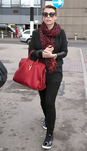 Coleen Rooney wore a red patterned scarf with her black ensemble while arriving for a flight at the airport.